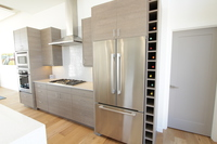 Thumb kitchen  contemporary style  custom laminate  grey   banded door  cubbie wine rack  frameless construction  chimney hood  micro oven cabinet
