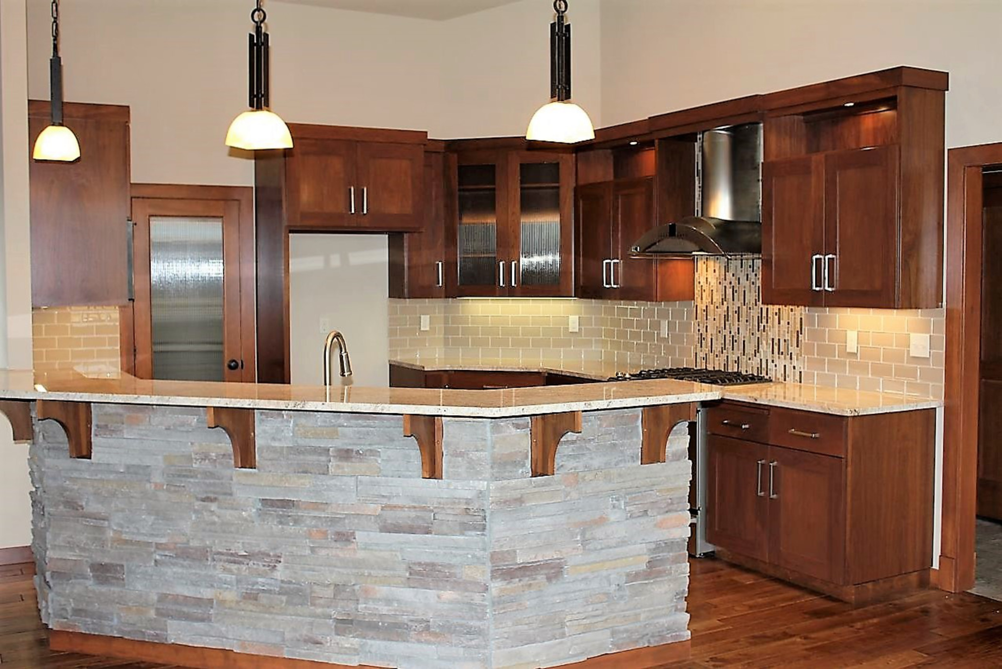 Kitchen  contemporary style  walnut  dark color  recessed panel  full overlay  rock island back   4 bar supports  reeded glass doors  chimney style hood with top  open space at top of the uppers