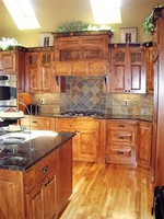 Thumb kitchen  craftsman style  knotty alder  medium color  raised panel  accent color  7 crown with blocks  bank of drawers  custom wood hood  glass grid top panels  posts   legs  standard overlay