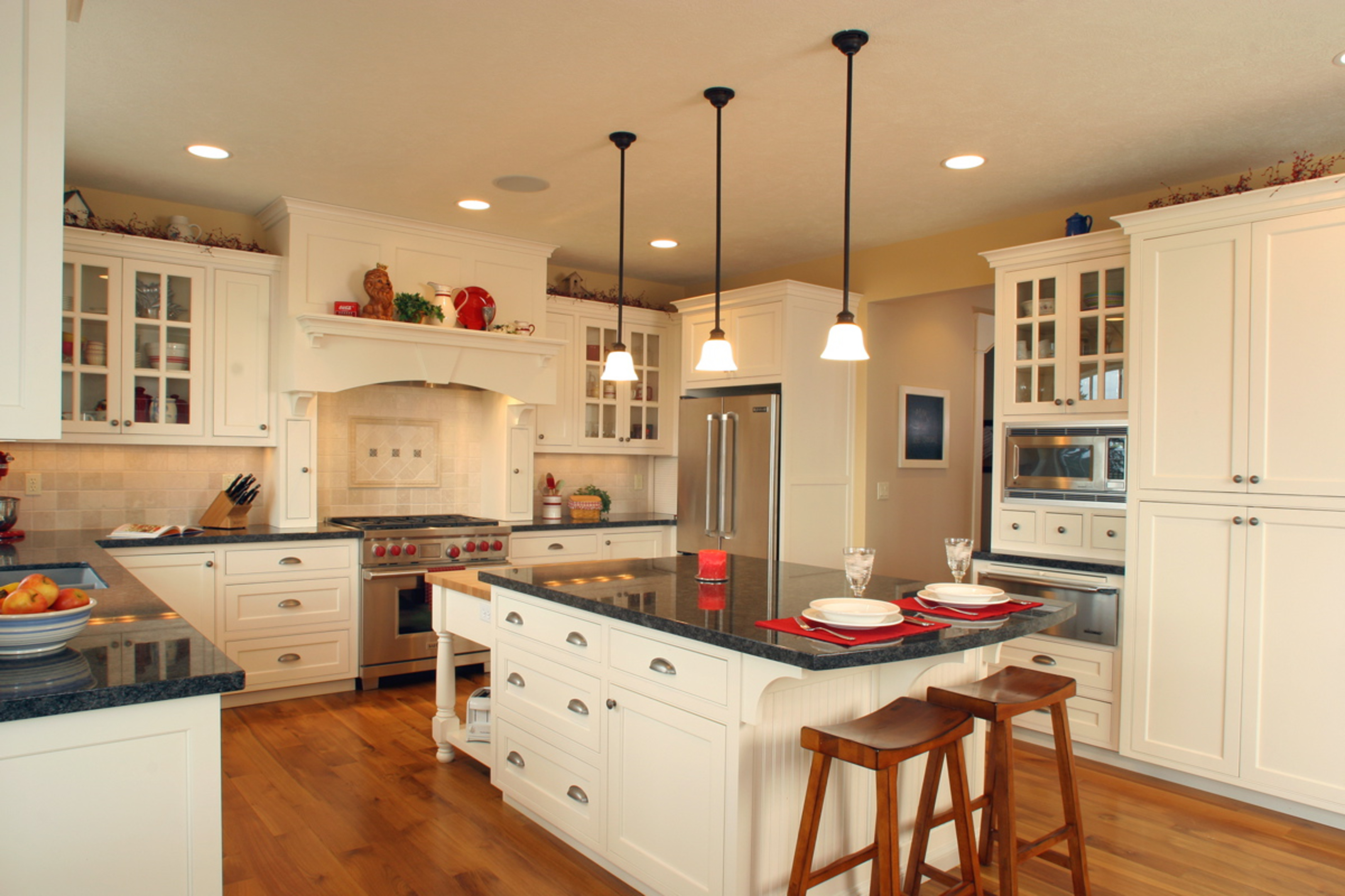 Kitchen  craftsman style  painted  recessed panel  flush mount  glass grid doors  wood hood  butcher block top  turned posts   legs  overhang on the end