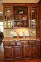 Thumb kitchen  traditional style  knotty alder  dark color  raised panel  three top drawers over 4 doors  plate rods  praire glass grid doors  full overlay