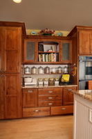 Thumb kitchen  traditional style  knotty alder  medium color  recessed panel  accent color painted island with sand through and wainscot  staggered heights  baking center  punched tin panels  wainscot backsplash