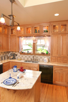 Thumb kitchen  traditional style  oak  light color  raised panel  glass doors at the top and over the window  upper to countertop with small drawers  small island  flush mount