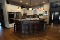 Thumb kitchen  traditional style  painted  recessed panel  accent color  grey or black stain  on hickory  angled island  glass grid doors  9 light or praire grid  staggered heights   3 bar supports  full overlay