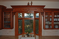 Thumb kitchen  traditional style  western maple  cherry color  raised panel  arched window valance with panels  glass doors with leaded seeded glass  carved crown  corbels  bay window  standard overlay