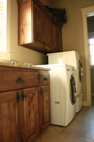 Thumb laundry or utility  traditional style  knotty alder  dark color  raised panel  1 edge  full overlay  upper above staggered height washer dryer  full overlay